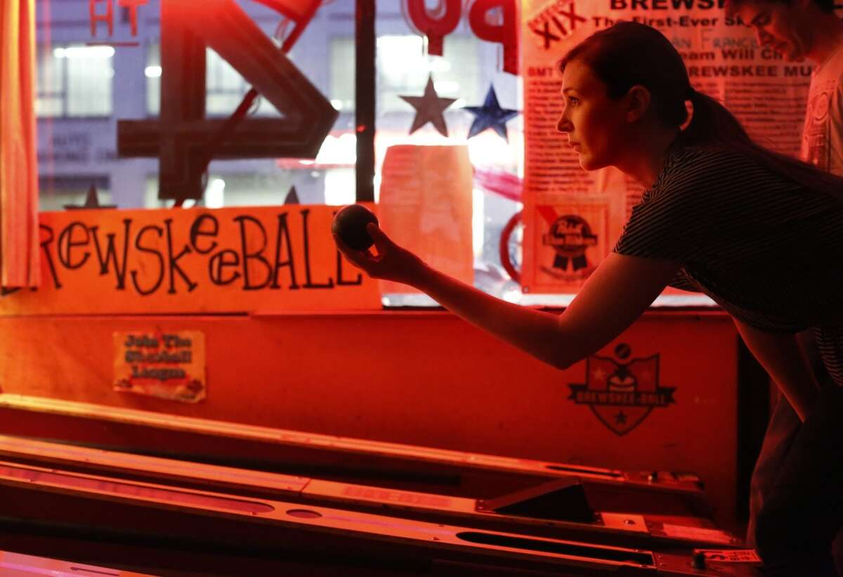 With a stroke as described by a friend to be as smooth as Ken Griffey Jr., Brewskee-Ball player Alison Siskelka with the team Circle for the Win, focuses on her roll at the Buckshot Bar and Gameroom in San Francisco, Calif. plays in the San Francisco Brewskee-Ball League at the Buckshot Bar and Gameroom in San Francisco, Calif.
