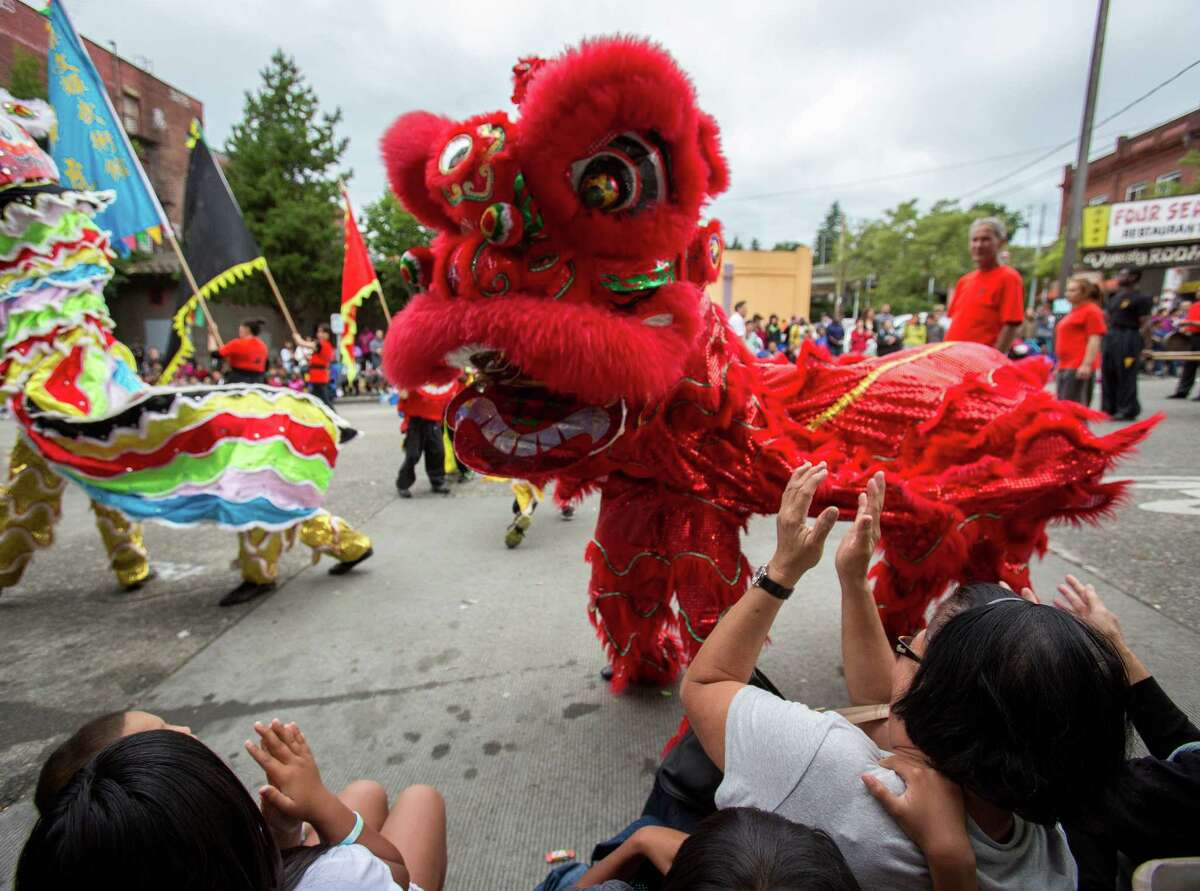 A lion entertains the crowd during the parade. Thousands lined the streets of the International District to watch the Chinatown Seafair Parade on July 20, 2014. The parade featured lion and dragon dancing, various floats, and performances from several seattle-based drill teams.