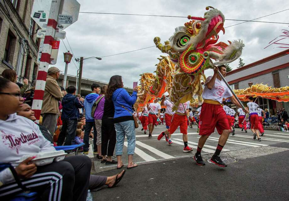 The 100-foot dragon weaves through the street during the parade. Thousands lined the streets of the International District to watch the Chinatown Seafair Parade on July 20, 2014. The parade featured lion and dragon dancing, various floats, and performances from several seattle-based drill teams. Photo: JOSHUA BESSEX, SEATTLEPI.COM / SEATTLEPI.COM