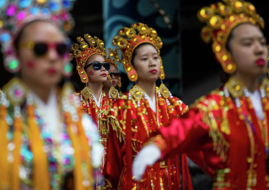 Members of the Seattle Chinese Girls Drill Team sport glasses as they march in the parade. Thousands lined the streets of the International District to watch the Chinatown Seafair Parade on July 20, 2014. The parade featured lion and dragon dancing, various floats, and performances from several seattle-based drill teams. Photo: JOSHUA BESSEX, SEATTLEPI.COM / SEATTLEPI.COM