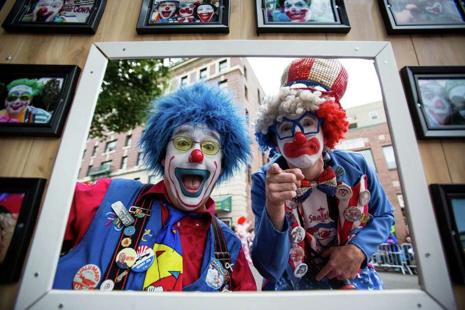 Clowns make faces through a frame they carried during the parade. Thousands lined the streets of the International District to watch the Chinatown Seafair Parade on July 20, 2014. The parade featured lion and dragon dancing, various floats, and performances from several seattle-based drill teams. Photo: JOSHUA BESSEX, SEATTLEPI.COM / SEATTLEPI.COM