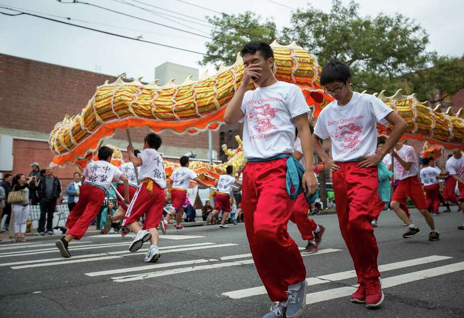 Weary marchers take a break from wielding the 100-foot dragon during the parade. Thousands lined the streets of the International District to watch the Chinatown Seafair Parade on July 20, 2014. The parade featured lion and dragon dancing, various floats, and performances from several seattle-based drill teams. Photo: JOSHUA BESSEX, SEATTLEPI.COM / SEATTLEPI.COM