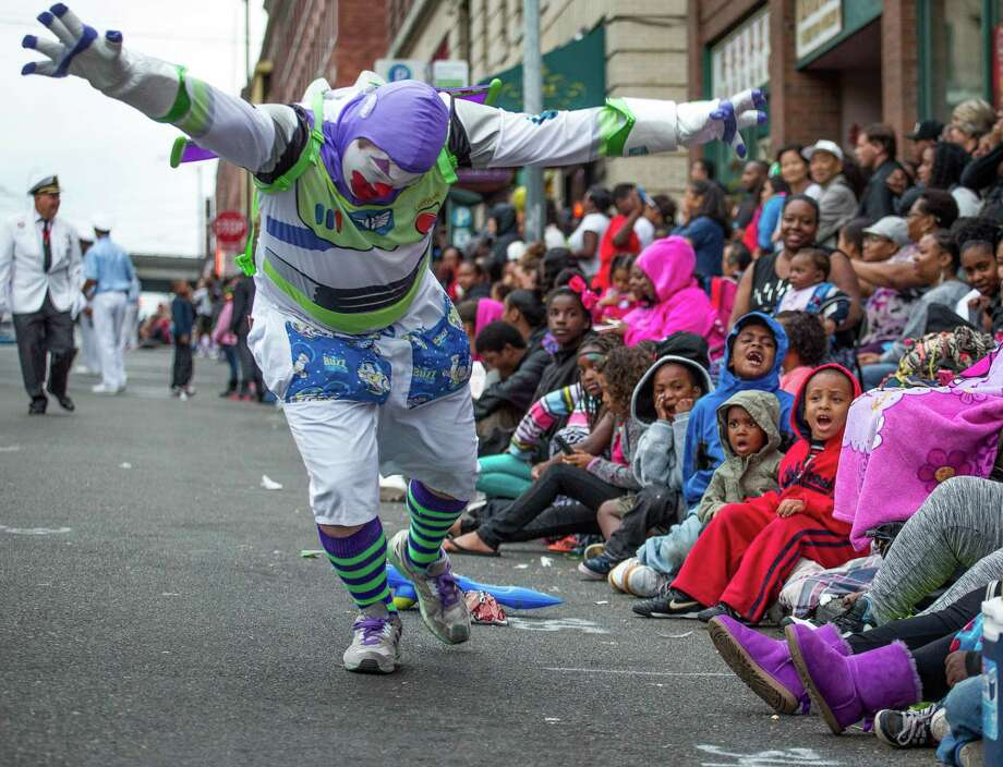 A clown dressed as Buzz Lightyear entertains children during the Chinatown Seafair Parade. Thousands lined the streets of the International District to watch the Chinatown Seafair Parade on July 20, 2014. The parade featured lion and dragon dancing, various floats, and performances from several seattle-based drill teams. Photo: JOSHUA BESSEX, SEATTLEPI.COM / SEATTLEPI.COM