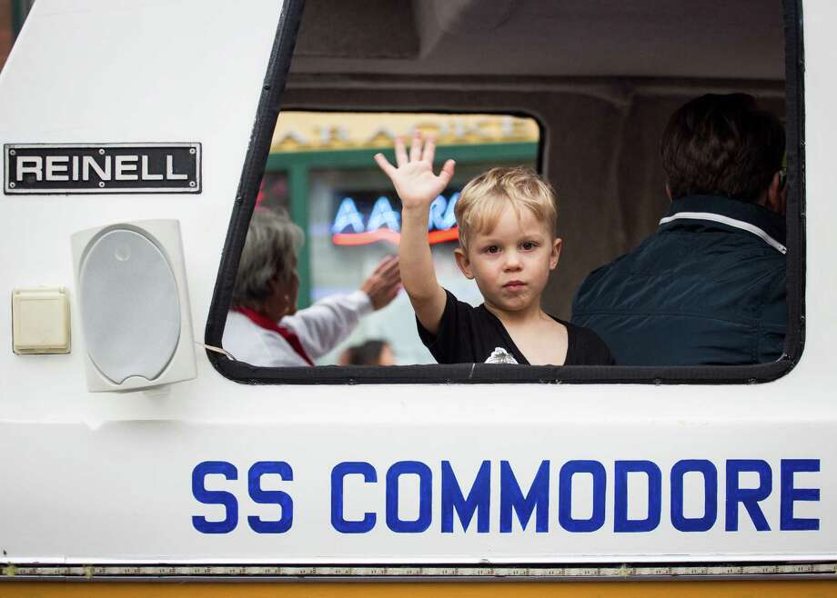 A young boy waves to the crowd from a yacht-themed float. Thousands lined the streets of the International District to watch the Chinatown Seafair Parade on July 20, 2014. The parade featured lion and dragon dancing, various floats, and performances from several seattle-based drill teams. Photo: JOSHUA BESSEX, SEATTLEPI.COM / SEATTLEPI.COM