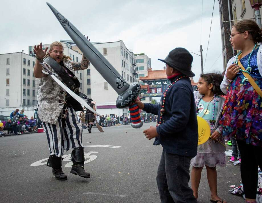 A Seafair pirate surrenders to a young boy with an inflatable sword during the parade. Thousands lined the streets of the International District to watch the Chinatown Seafair Parade on July 20, 2014. The parade featured lion and dragon dancing, various floats, and performances from several seattle-based drill teams. Photo: JOSHUA BESSEX, SEATTLEPI.COM / SEATTLEPI.COM