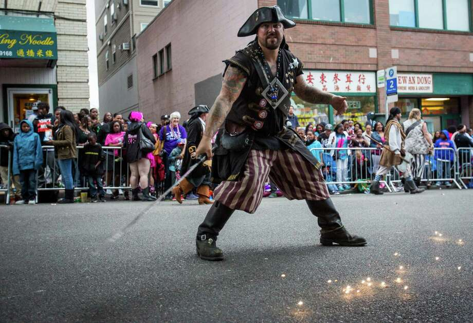 A Seafair pirate makes sparks fly with his sword. Thousands lined the streets of the International District to watch the Chinatown Seafair Parade on July 20, 2014. The parade featured lion and dragon dancing, various floats, and performances from several seattle-based drill teams. Photo: JOSHUA BESSEX, SEATTLEPI.COM / SEATTLEPI.COM