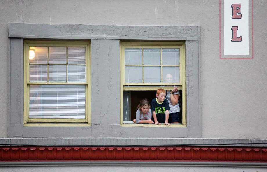 Children watch the parade from a window. Thousands lined the streets of the International District to watch the Chinatown Seafair Parade on July 20, 2014. The parade featured lion and dragon dancing, various floats, and performances from several seattle-based drill teams. Photo: JOSHUA BESSEX, SEATTLEPI.COM / SEATTLEPI.COM