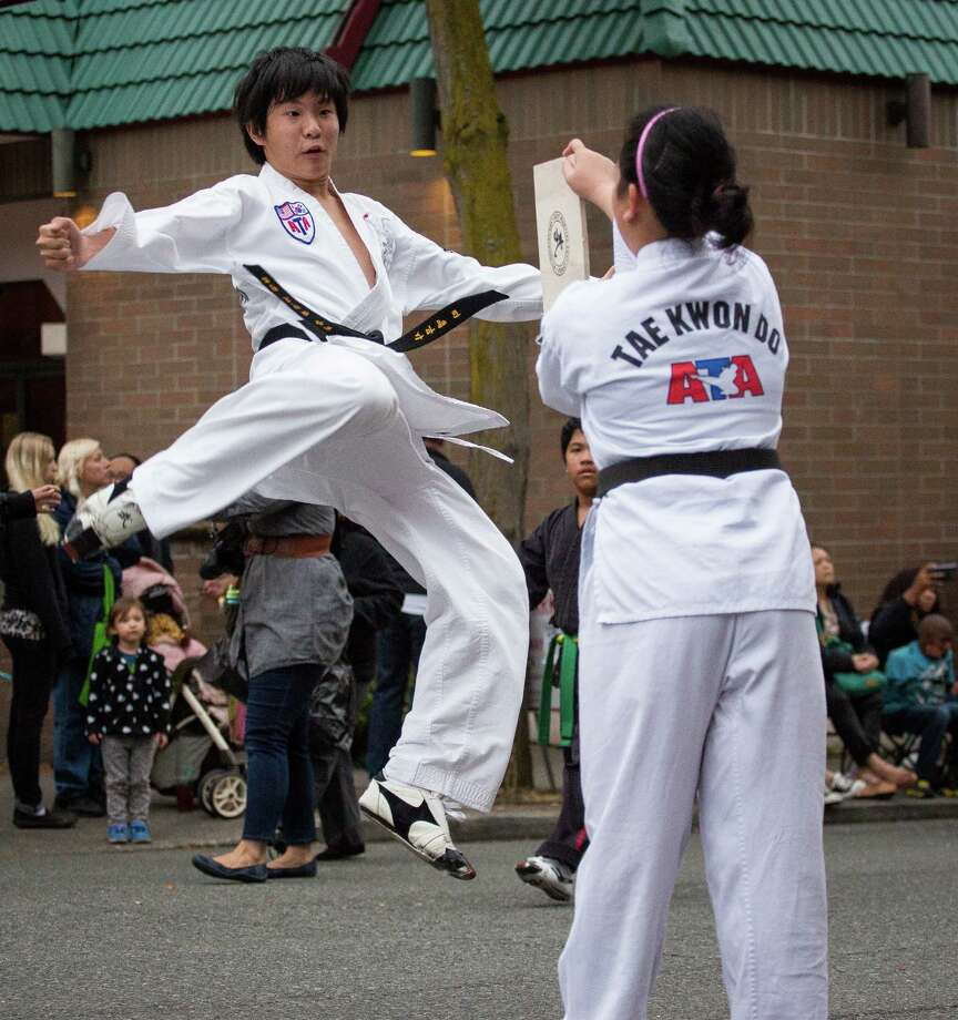 A young boy leaps to break a piece of wood in half during a Tae Kwon Do demonstration at the parade. Thousands lined the streets of the International District to watch the Chinatown Seafair Parade on July 20, 2014. The parade featured lion and dragon dancing, various floats, and performances from several seattle-based drill teams. Photo: JOSHUA BESSEX, SEATTLEPI.COM / SEATTLEPI.COM