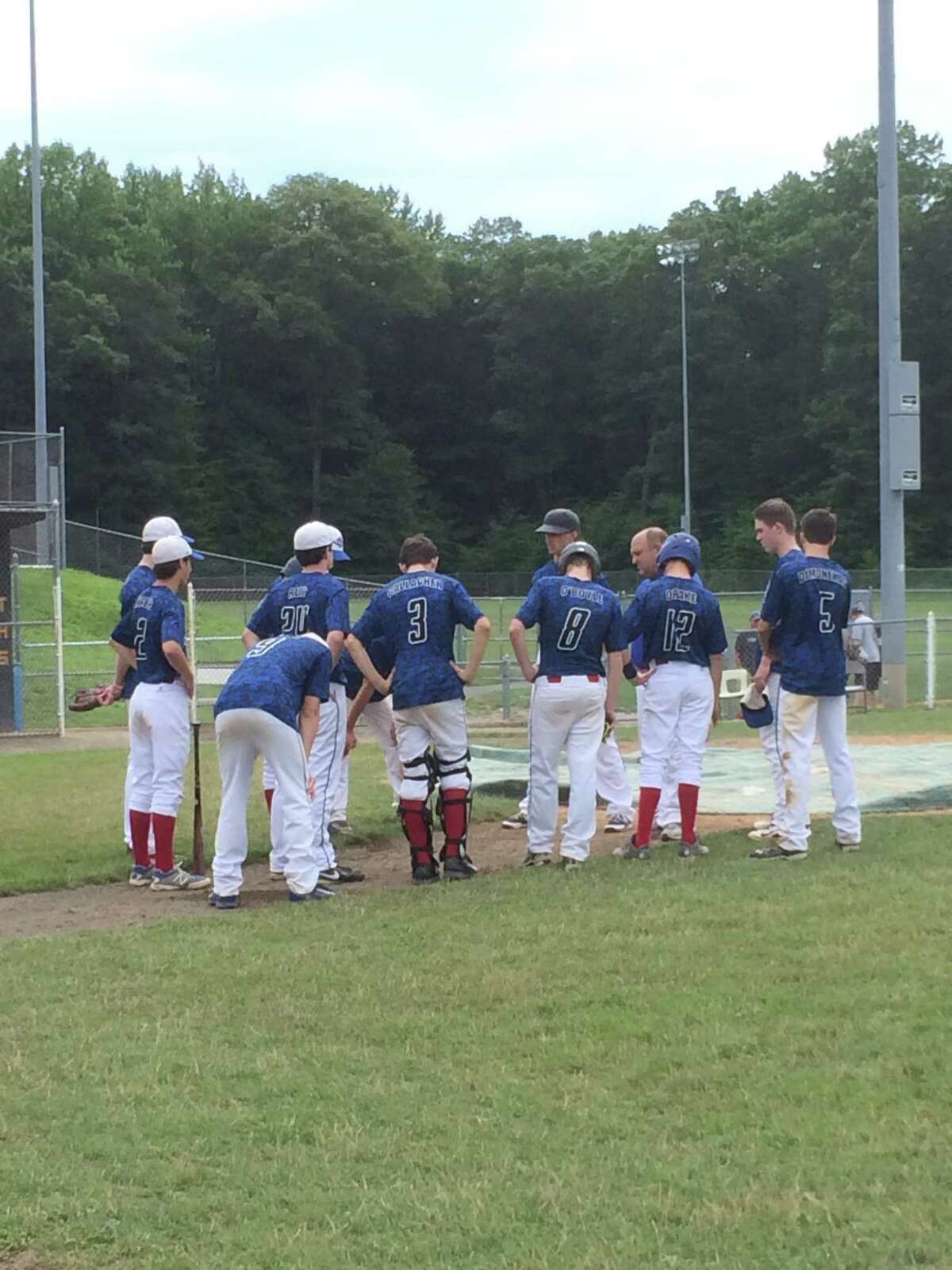 The Darien-New Canaan Junior Legion baseball team stands with coaches Michael Patrona and Mike Alfieri after its final game of the 2014 season, a 1-0 loss at first-place Trumbull on Saturday, July 19.