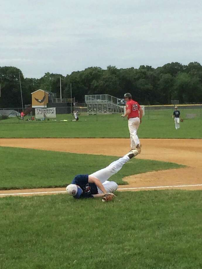 Darien-New Canaan Junior Legion first baseman Ryan Radecki makes a diving catch to end the second inning of a regular season game at Trumbull on Saturday, July 19. Photo: Andrew Callahan / Darien News