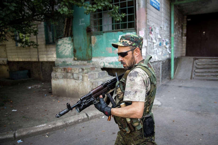 """No. 8: 'Considerable losses'Paul contends the separatists in eastern Ukraine hammered the Ukrainian government """"in the week before the plane was downed."""" A pro-Russia rebel, shown here, patrols a residential area close to the central railway station in Donetsk.  • Crisis shows cracks in old Soviet bloc Photo: Rob Stothard, Getty Images / 2014 Getty Images"""