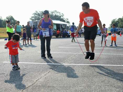 From right, Juan Farias and his wife, Rocio Farias, watch their son Mateo Farias, 1, try to jump rope during the Jump into Fitness event on Saturday, July 19, 2014, at Brooks City Base in San Antonio. The Farias family has been coming to the yearly event since it began five years ago. Photo: Timothy Tai, San Antonio Express-News / © 2014 San Antonio Express-News