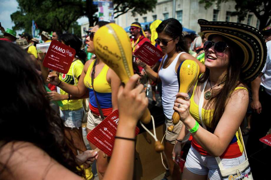 Natalia Giraldo, right, 18, dances to the rhythm of Grupo Gale's music with maracas in hand during the Colombian Fest 2014 in Houston, Sunday, July 20, 2014. Photo: Marie D. De Jesus, Houston Chronicle / © 2014 Houston Chronicle