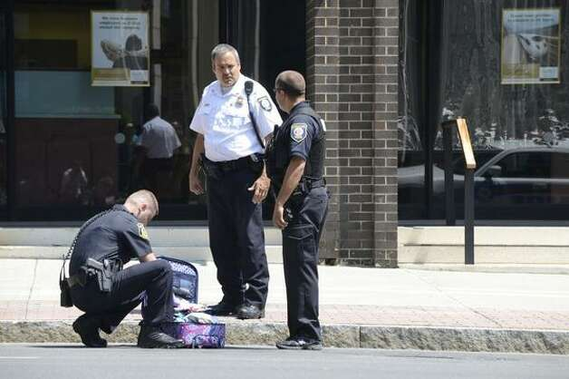 Albany police check at piece of luggage that was left abandoned in front of 41 State St. on Monday. Police briefly closed the area to traffic while they determined that there was nothing dangerous about the package. (Will Waldron / Times Union)
