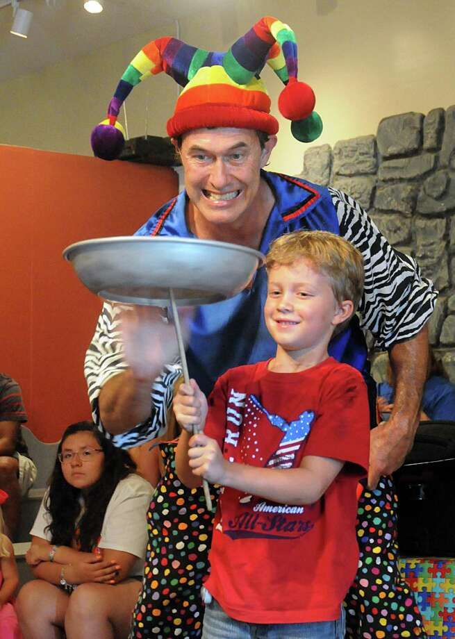 Juggler Claude Sims, of Cypress, spins a plate being balanced by Evan Wieberg, of The Woodlands, during The Woodlands Children's Museum, 4775 W. Panther Creek Drive, fourth anniversary celebration. Face painting, balloon art, magicians and snacks were part of the activities.  Photo: David Hopper, For The Chronicle / freelance