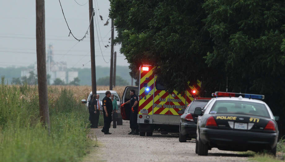 Police and emergency personnel attend a scene Monday July 21, 2014 at 8219 Somerset Road where the body of a man was found near a corn field inside of a white sedan. The body was decomposed, but police were able to identify the man based on information found in the car. Photo: JOHN DAVENPORT, San Antonio Express-News / ©San Antonio Express-News/John Davenport