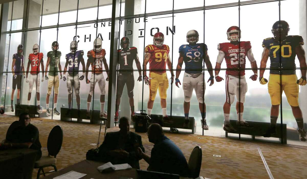 Window art of football players adorn the windows at the hotel hosting the NCAA college Big 12 Conference football media days in Dallas, Monday, July 21, 2014. (AP Photo/LM Otero)