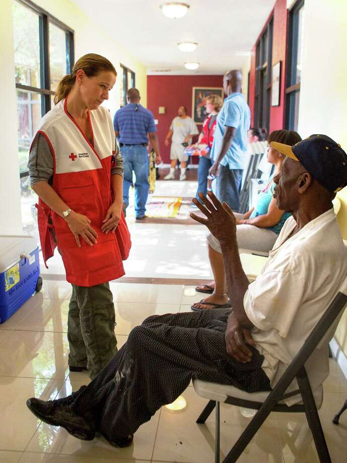 "Loly Thomas, with the American Red Cross, left, talks with, Robert Reed, right, after a 3-alarm fire tore through his apartment in the 6100 block of Antoine, north of Tidwell, Monday, July 21, 2014, in Houston. The fire displaced dozens of residents as it tore through the three-story complex. ""It's gone,"" he said of his apartment. Photo: Cody Duty, Houston Chronicle / © 2014 Houston Chronicle"