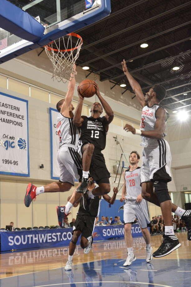Rockets defenders converge on Nets guard Marquis Teague. Photo: Fernando Medina, NBAE/Getty Images / 2014 NBAE