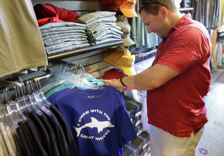 In this July 2, 2014 photo, vacationer Mark McCurdy, of Everett, Mass., examines shark-themed clothing at the Chatham Clothing Bar in Chatham, Mass. Growing sightings of great white sharks off Cape Cod are generating business for local entrepreneurs as residents and tourists seek a glimpse of the offshore predators -- or purchase their shark-themed memorabilia and apparel. Photo: Steven Senne, AP / AP