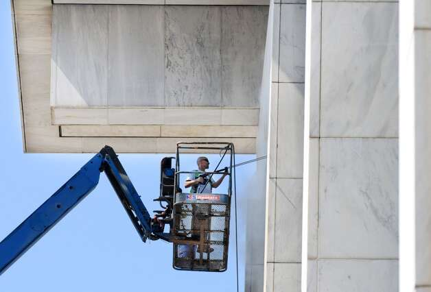 Pat Malatesta of Niskayuna, with the Office of General Services, power washes the Legislative Office Building's exterior walls Monday morning, July 21, 2014, at the Empire State Plaza in Albany, N.Y. (Will Waldron/Times Union) Photo: Will Waldron, Albany Times Union