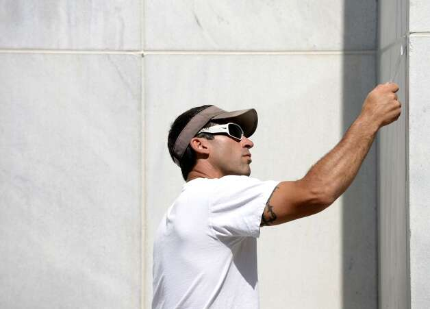 Mike Novak of New Scotland, with the Office of General Services, applies caulk to seams on Legislative Office Building's exterior walls Monday morning, July 21, 2014, at the Empire State Plaza in Albany, N.Y. (Will Waldron/Times Union) Photo: Will Waldron, Albany Times Union
