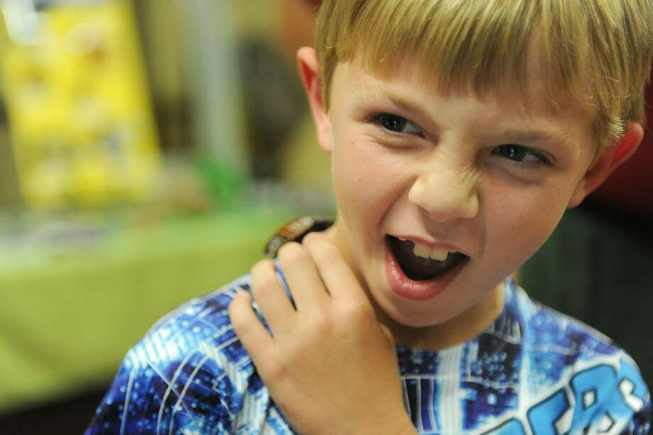 Educational enroachment:Seven-year-old Rayden Kasner fights the urge to flick a Madagascar Hissing Cockroach off his back in Evansville, Ind. Rayden allowed the roach to crawl on his arm, but it didn't stop there. (Bug Fest at Wesselman Woods Nature Center.) Photo: Erin McCracken, Associated Press