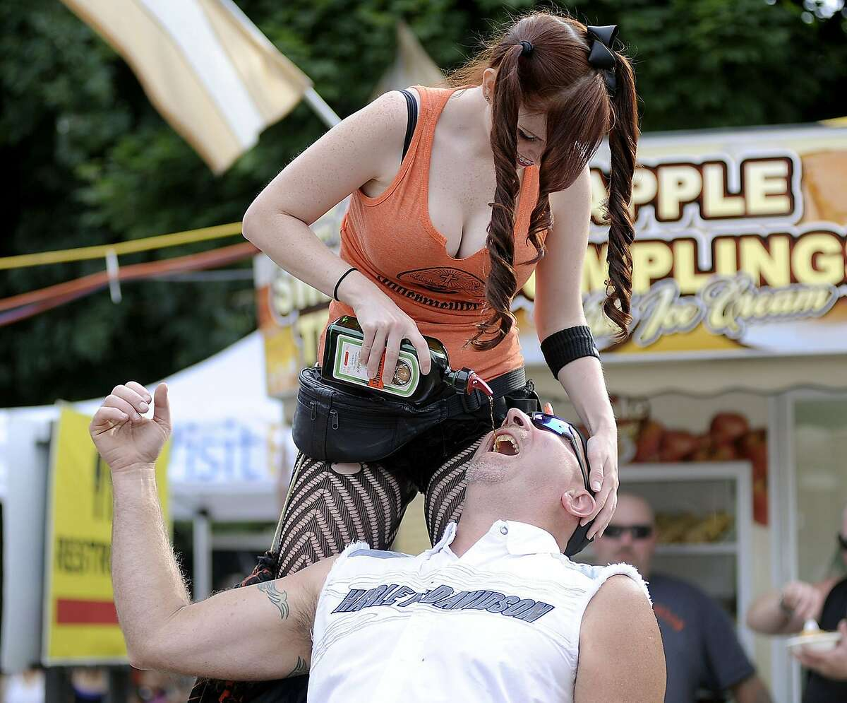 Tragically, no one remembered to bring the shot glasses: Amber Phelps pours Jagermeister into the mouth of Steve Wig in Erie, Pa., during the Roar on the Shore Motorcycle Rally.