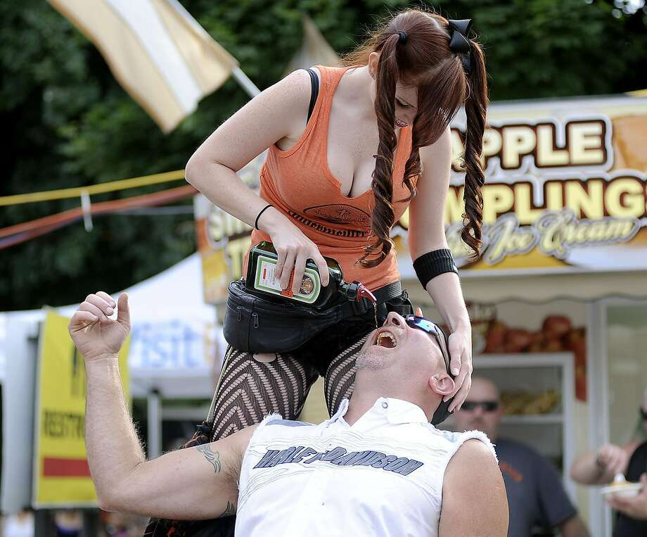 Tragically, no one remembered to bring the shot glasses:Amber Phelps pours Jagermeister   into the mouth of Steve Wig in Erie, Pa., during the Roar on the Shore Motorcycle Rally. Photo: Emily Kask, Associated Press