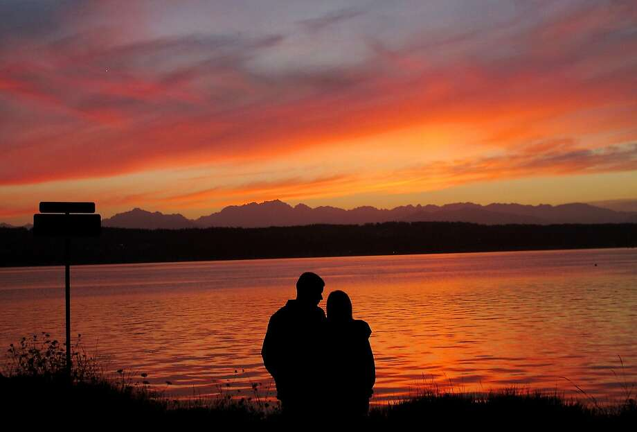 Sunset gazers: Marco Lavario and Kia Ashley share a romantic moment at the boat launch in Tracyton, Wash. Photo: Meegan M. Reid, Associated Press