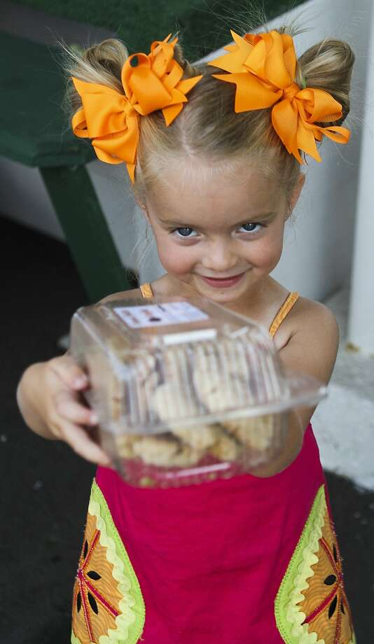 Two ribbons and a smile: Four-year-old Olivia Dell'Aglio offers cookies to shoppers at the Co-Op Farmer's Market in Scranton, 