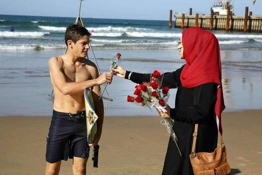"Beach blooms: A volunteer hands a rose to a surfer during the ""Petals for Palestine"" Peace Project at the North 