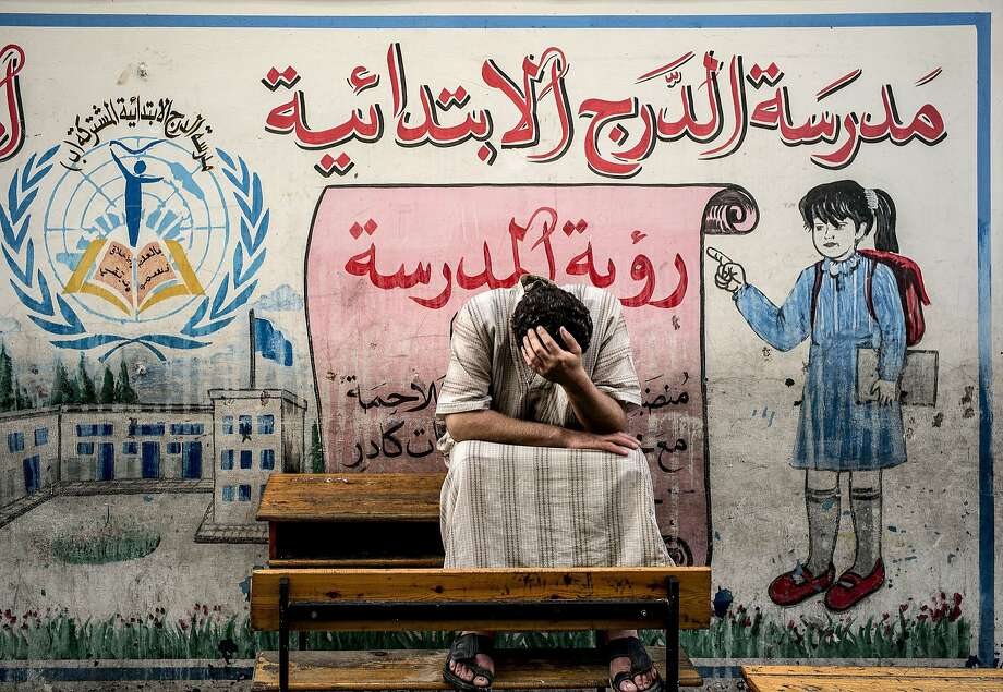 Sanctuary from the hostilities: A displaced Palestinian from the Shejaiya neighborhood in the Gaza Strip sits on a bench at a U.N. 