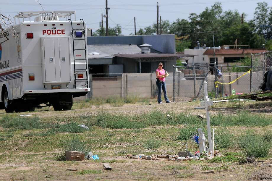 In a Saturday, July 19, 2014 photo, Albuquerque police work at the scene where two men were found dead in a open area just north of Central Avenue at 60th Street. Three teenagers are being held in Bernalillo County detention facilities a day after allegedly killing the two sleeping men in an open field in an attack so violent it left the victims unrecognizable, police spokesman Simon Drobik said. A third man said he was able to escape. (AP Photo/Albuquerque Journal, Jim Thompson) MANDATORY CREDIT Photo: Jim Thompson, Associated Press