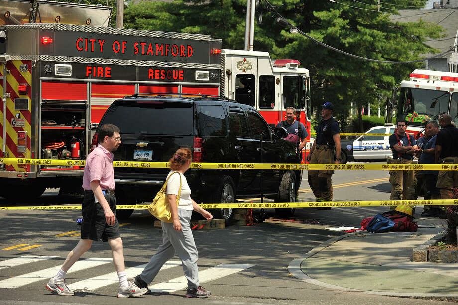 Pedestrians walk across Hoyt Street watching emergency personnel at the scene where Janice Pielert, 58, of Stamford, was struck and killed by an SUV driven by Natalie Gainer at the intersection of Hoyt and Summer streets in Stamford, Conn. around 12:45 p.m. Monday, July 21, 2014. Police said Pielert who was crossing Hoyt Street. The SUV was heading south on Summer Street and turning east on Hoyt Street when it hit the Pielert. Photo: Jason Rearick / Stamford Advocate