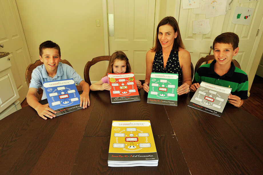 "From left: Nicky, Annie, Suzanne, and Charlie Wind pose with the book series, ""The SMART Playbook,"" at their home in Cos Cob, Conn., on Monday, July 21, 2014. The series, written mostly by Suzanne with help from her children, is made up of five workbooks that teach children manners and social etiquette in the digital age. Photo: Jason Rearick / Stamford Advocate"