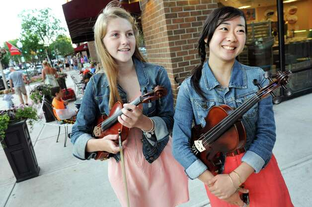Buskers Ali Genevich, 16, left and Seina Shirakura, 18, both classically-trained violinists, play fiddle tunes on Broadway on Thursday, July 10, 2014, in Saratoga Springs, N.Y. (Cindy Schultz / Times Union) Photo: Cindy Schultz / 00027672A