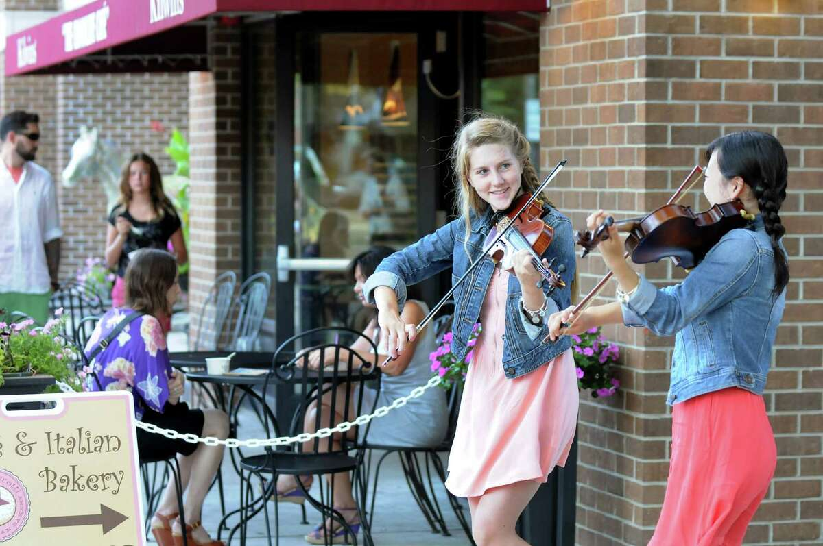 Buskers Ali Genevich, 16, center, and Seina Shirakura, 18, both classically-trained violinists, play fiddle tunes for tips on Broadway on Thursday, July 10, 2014, in Saratoga Springs, N.Y. (Cindy Schultz / Times Union)