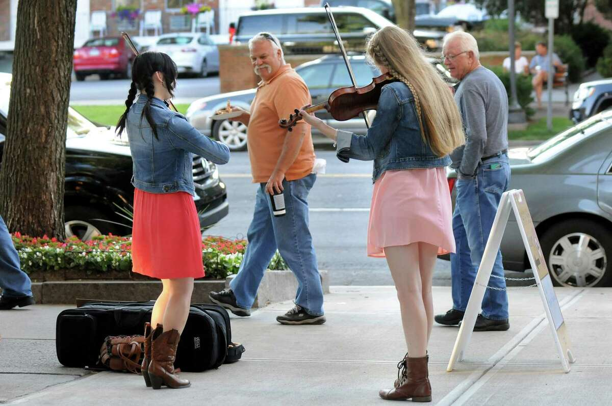 Buskers Seina Shirakura, 18, left, and Ali Genevich, 16, both classically-trained violinists, play fiddle tunes for tips on Broadway on Thursday, July 10, 2014, in Saratoga Springs, N.Y. (Cindy Schultz / Times Union)