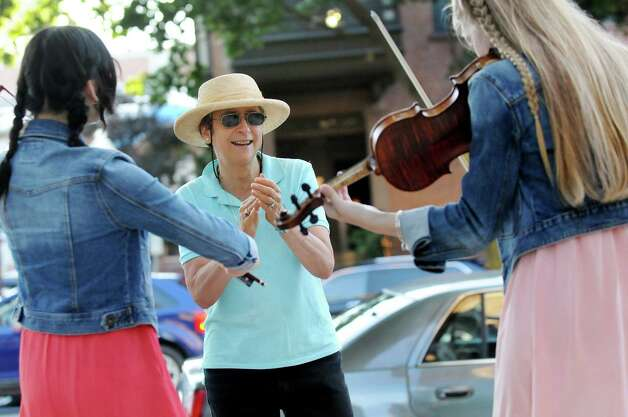 Betsy Tick of Saratoga Springs, center, claps along to the music of buskers Seina Shirakura, 18, left, and Ali Genevich, 16, both classically-trained violinists who play fiddle tunes for tips, on Broadway on Thursday, July 10, 2014, in Saratoga Springs, N.Y. (Cindy Schultz / Times Union) Photo: Cindy Schultz / 00027672A