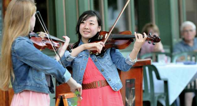 Buskers Seina Shirakura, 18, center, and Ali Genevich, 16, both classically-trained violinists , play fiddle tunes for tips on Broadway on Thursday, July 10, 2014, in Saratoga Springs, N.Y. (Cindy Schultz / Times Union) Photo: Cindy Schultz / 00027672A