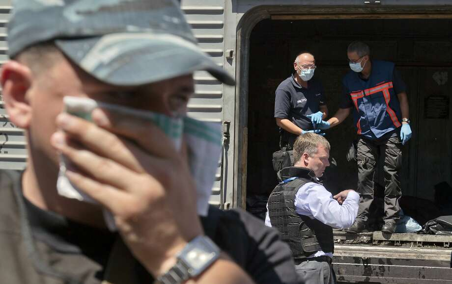 A man covers his face with a rag due to the smell, as deputy head of the OSCE mission to Ukraine Alexander Hug, center right, stands outside a refrigerated train as members of Netherlands' National Forensic Investigations Team inspect bodies, seen in plastic bags, 15 kilometers (9 miles) from the crash site of Malaysia Airlines Flight 17, in Torez, eastern Ukraine, Monday, July 21, 2014. Another 21 bodies have been found in the sprawling fields of east Ukraine where Malaysia Airlines Flight 17 was downed last week, killing all 298 people aboard. International indignation over the incident has grown as investigators still only have limited access to the crash site and it remains unclear when and where the victims' bodies will be transported. (AP Photo/Vadim Ghirda) Photo: Vadim Ghirda, Associated Press