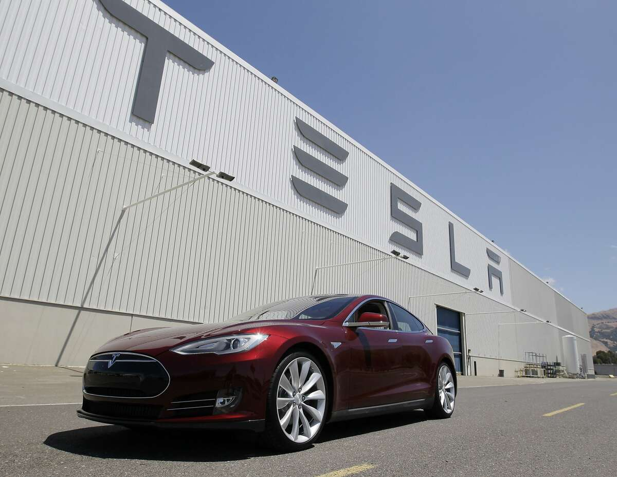 This June 22, 2012 file photo shows a Tesla Model S driving outside the Tesla factory in Fremont, Calif. Electric-car company Tesla Motors has filed notice it intends to sue New Jersey over a ruling that would stop it from selling its vehicles in the state within two weeks. Palo Alto, Calif.-based Tesla claims it was unfairly targeted in March 2014 when the state Motor Vehicle Commission amended its regulations. The regulations require new-car dealers to have franchise agreements before they can be licensed. That prohibits companies from using a direct-sales model as Tesla does. (AP Photo/Paul Sakuma, File)