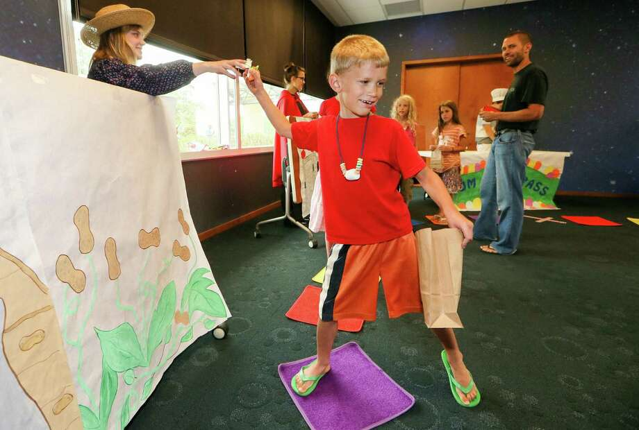 Zion Whitten, 6, takes a piece of candy from Alle Wolfer, 18,  in a life-sized game of Candy Land Saturday at the Schertz Public Library. Photo: Marvin Pfeiffer / Northeast Herald / EN Communities 2014