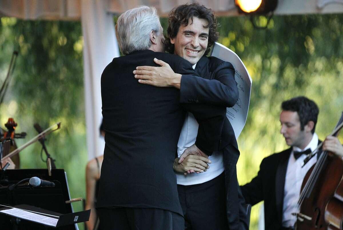 Carlo Ponti hugs composer Daniel Brewbaker part way through conducting a tribute concert