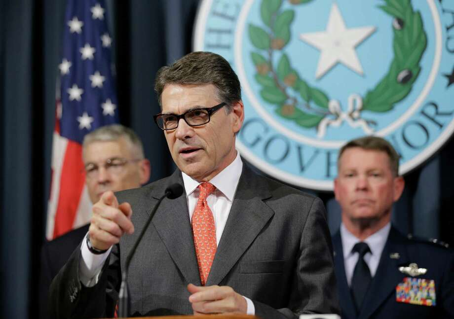 Gov. Rick Perry, center, speaks during a news conference in the Governor's press room, Monday, July 21, 2014, in Austin, Texas. Gov. Perry announced he is deploying up to 1,000 National Guard troops over the next month to the Texas-Mexico border to combat criminals that Republican state leaders say are exploiting a surge of children and families entering the U.S. illegally.  (AP Photo/Eric Gay) Photo: Eric Gay, STF / AP