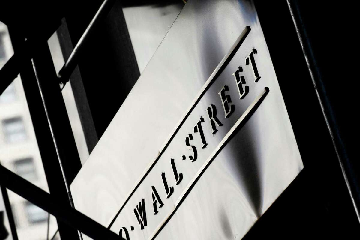 FILE - This July 15, 2013 file photo shows a sign for Wall Street outside the New York Stock Exchange, in New York. World stock markets remained on the back foot Monday, July 21, 2014, as tensions grew between Russia and the West over the downing of an airliner in eastern Ukraine. (AP Photo/Mark Lennihan, File) ORG XMIT: NYBZ142
