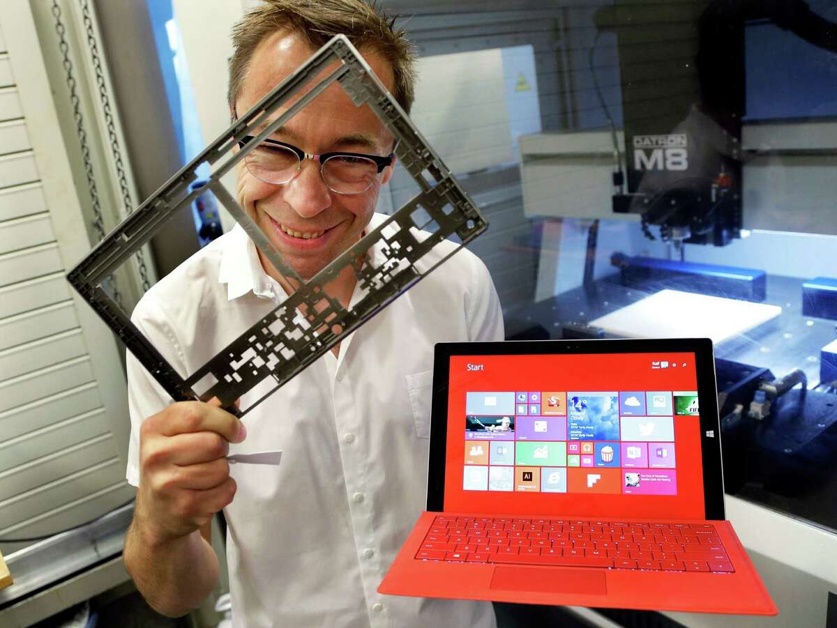 In this photo taken July 3, 2014, Ralf Groene, chief designer for the Microsoft Surface tablet computer, poses for a photo with a Surface 3 Pro tablet, right, in front of a milling machine used to produce parts for the computer, like the one he is holding at left, in Redmond, Wash. As Microsoft competes with Apple and other companies for hardware sales, the software giant has put a new emphasis on design. (AP Photo/Ted S. Warren) ORG XMIT: NYBZ201