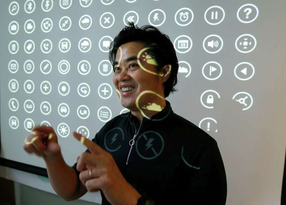 In this photo taken July 3, 2014, Albert Shum, who heads interaction design across a range of Microsoft products including personal computer operating systems, Xbox game consoles, and phones, poses for a photo in front of a projection of icons used by those systems, in Redmond, Wash. A former designer for shoemaker Nike, Shum was part of the team that revolutionized the Windows Phone design to feature the boxy, so-called ?