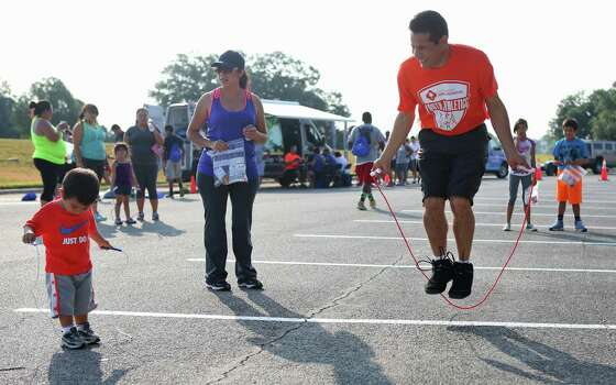 Juan Farias and wife Rocio watch son Mateo, 1, try to jump rope during the Jump into Fitness event last weekend at Brooks City Base. The family has participated in the program for five years. Photo: Timothy Tai / San Antonio Express-News / © 2014 San Antonio Express-News